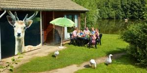 Gezin zit buiten aan tafel voor vakantiehuisje van vakantiepark Dierenbos