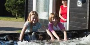 Vrouw in deuropening van vakantiehuisje van Vakantiepark Slagharen, twee kinderen bij de jacuzzi