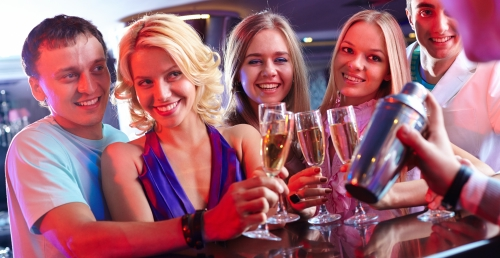 Barman maakt cocktain, twee jonge mannen, drie jonge vrouwen met champagne vieren Oud & Nieuw