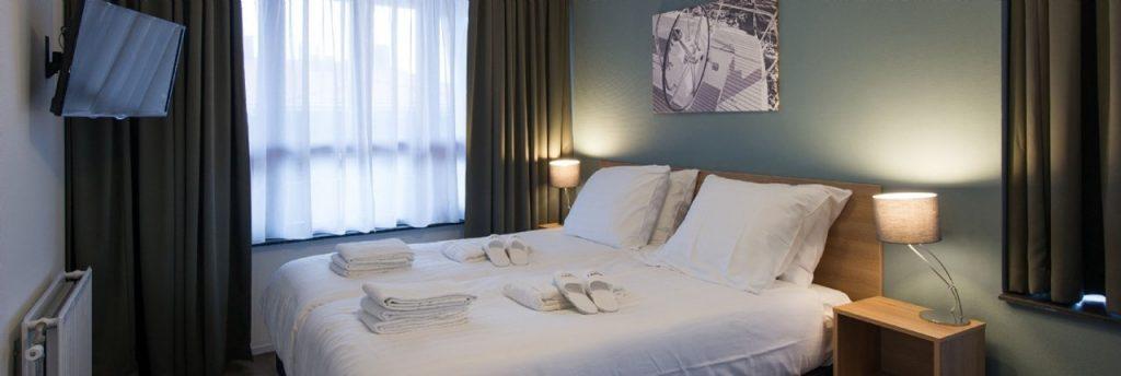 Bedlinnen afnemen is bij Landal GreenParks verplicht. Op deze foto ziet u een mooie slaapkamer in een accommodatie van Landal waarbij gekozen is voor een luxe arrangement, de bedden zijn opgemaakt en er liggen handdoeken en badslippers klaar voor de gasten.