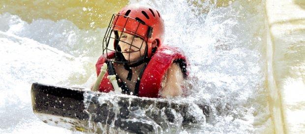 Kind gaat met hoge snelheid door wildwaterbaan tijdens de Cool Factor: Wild Water Rafting activiteiten in het Aqua Mundo zwemparadijs van Center Parcs De Kempervennen