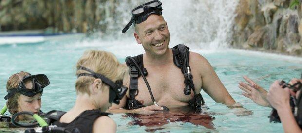 Kinderen gaan onder begeleiding van een duikinstructeur duiken in het Aqua Mundo van Center Parcs De Kempervennen