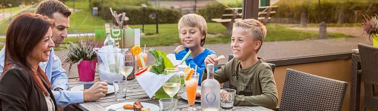 Gezin met kinderen zit op het terras bij een parkrestaurant van Landal Greenparks en genieten van lekker eten en drinken. Zij gingen voordeliger uit eten dankzij het Uiteten-arrangement van Landal GreenParks