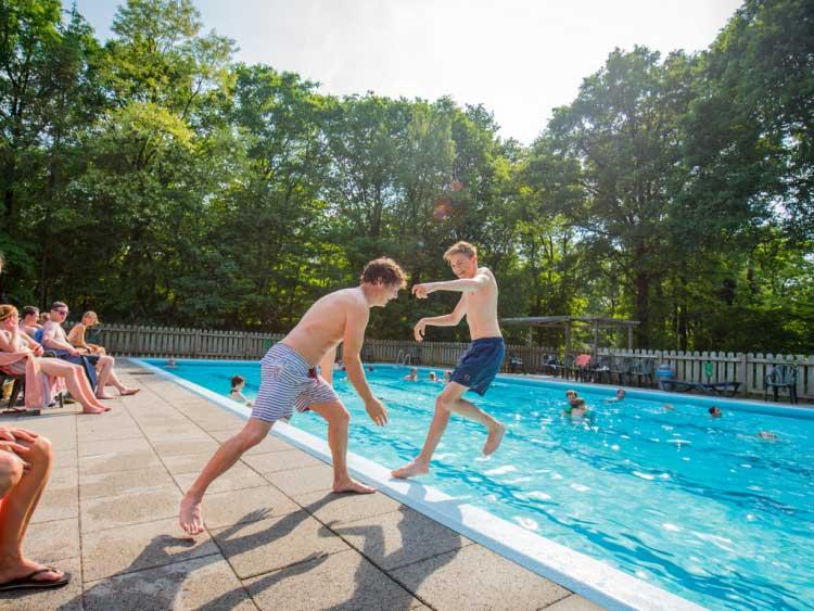 Parkgasten genieten van de zon en zijn aan het zwemmen bij het openluchtzwembad van Landal Rabbit Hill
