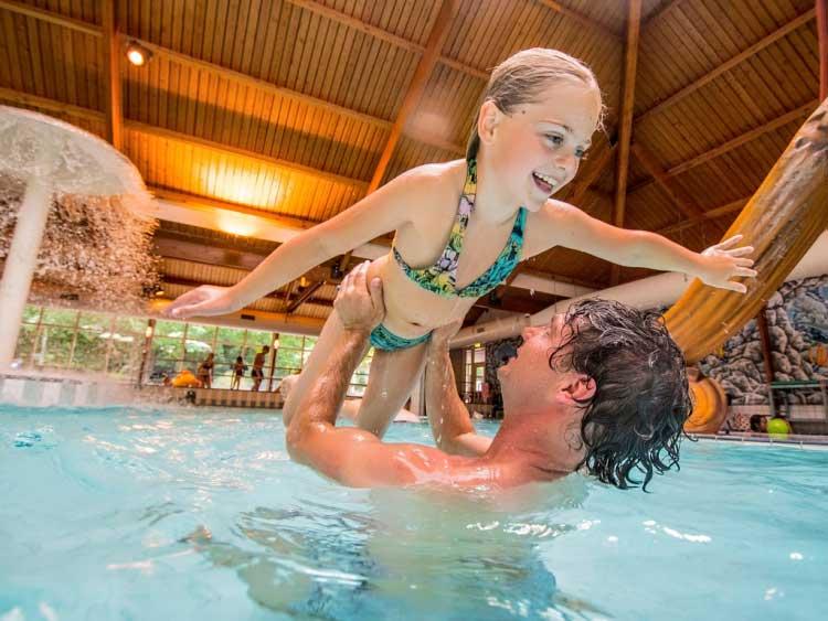 Dochter en vader hebben veel zwemplezier in het overdekt zwembad van Landal Rabbit Hill