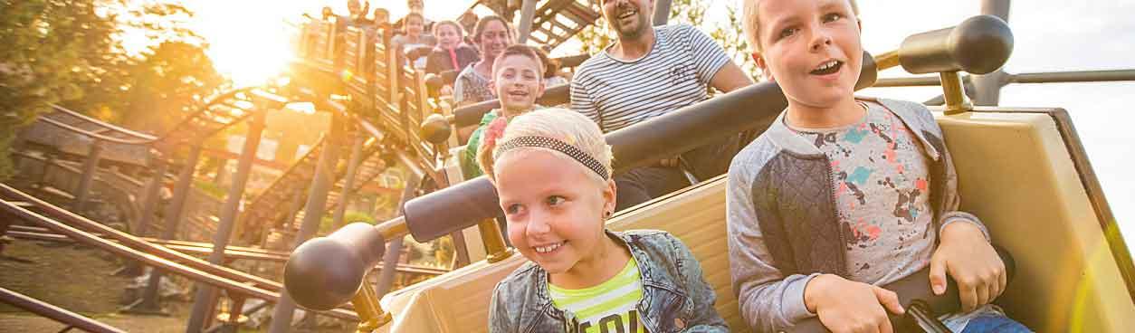 Mensen hebben veel plezier tijdens hun achtbaanrit in de Mine-Train van Attractiepark Slagharen