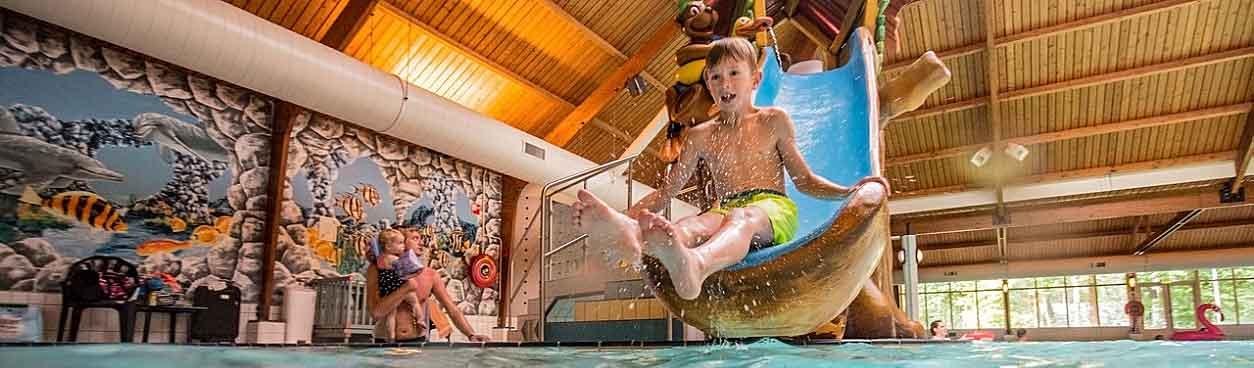 Jongen gaat van de kinderglijbaan af in het overdekt zwembad van Landal Miggelenberg