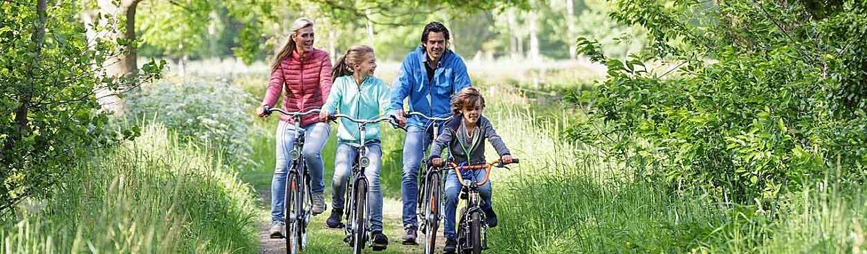 Bij Center Parcs kun je als gezin familiekorting krijgen. Voor senioren is er 55+ korting. Het gezin op de foto geniet in ieder geval van een heerlijke vakantie en maakt een leuke fietstocht door de natuur.