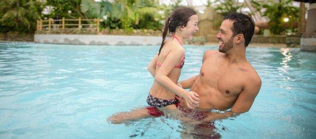 Vader en dochter hebben veel zwemplezier in het golfslagbad van het Aqua Mundo zwemparadijs van Center Parcs De Kempervennen