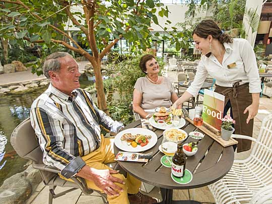 Man en vrouw krijgen hun eten van serveerster bij het Grand Café