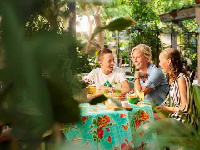 In de tropische Market Dome kun je bij één van de restaurants lekker eten en drinken. Deze moeder met haar kinderen hebben het in ieder geval goed naar hun zin tijdens gezellig uit eten gaan.