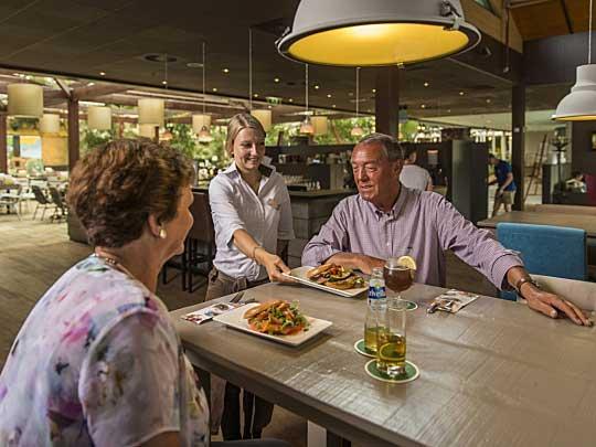 Vrouw en man krijgen hun eten bij Steaks & Burgers