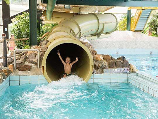 Jongen beleeft veel zwemplezier met de glijbaan in het subtropisch zwemparadijs