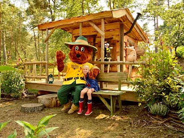 Meisje en Bollo de Beer zitten op een bankje voor het Bollo de Beer huisje van een Landal park