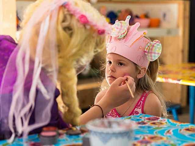 Meisje laat zich schminken door een medewerkster van Landal in de Kinderclub
