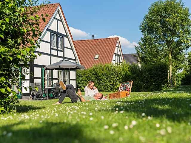 Vrouw en man genieten van het zonnetje en gezellig picknick in het gras bij hun vakantiewoning bij een Landal park in Limburg