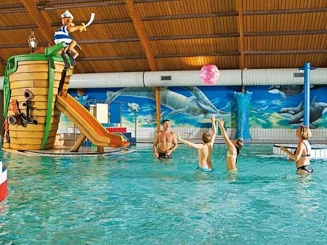 Gezin met kinderen aan het genieten van zwemplezier in het overdekte zwembad op een Landal vakantiepark