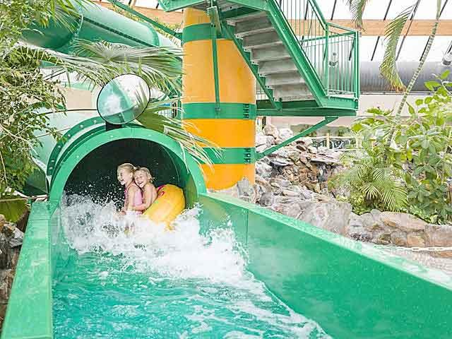 Twee kinderen in een luchtband van de glijbaan af in het subtropisch zwemparadijs van een Landal park