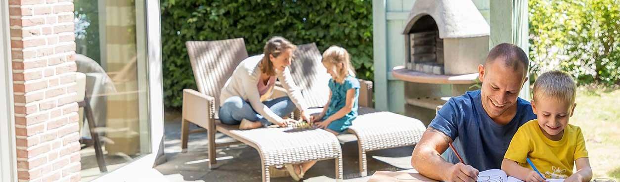 Vader met zoon aan het kleuren, moeder met dochter spelletje aan het spelen bij cottage van een Center Parcs vakantiepark