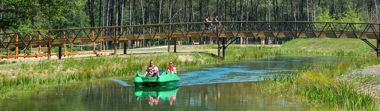 Vader en moeder met kind in een waterfiets, twee mensen op de fiets over een brug over het water bij een Center Parcs vakantiepark