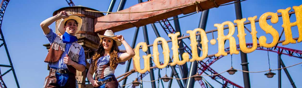 Slagharen blijft tot nader order gesloten i.v.m. beleid Corona, Foto: Man en vrouw in cowboykleding voor het uithangbord van de Gold Rush attractie in Attractiepark Slagharen