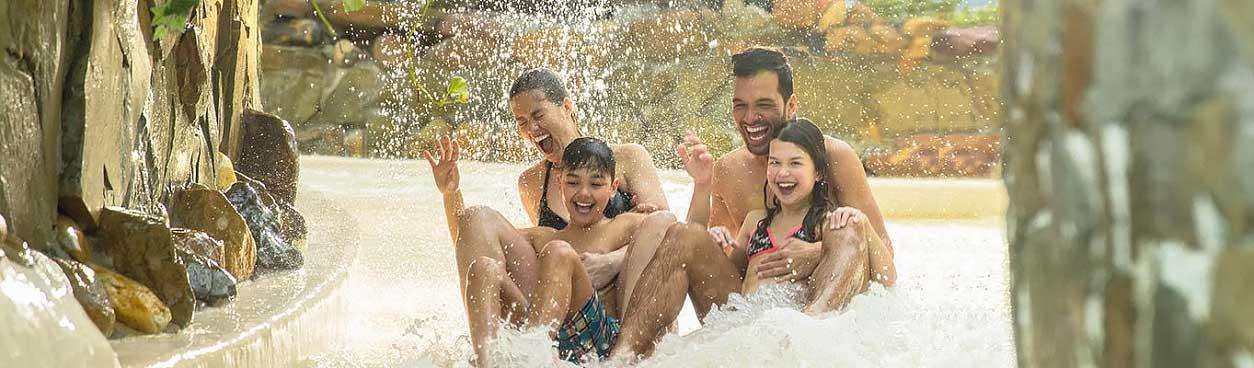 Is Center Parcs Waanzinnige Woensdag echt voordeliger? Foto: Gezin met kinderen heeft glijbaanplezier in het Aqua Mundo subtropisch zwemparadijs.